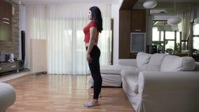 Sexy attraktive Frau, die Fernseheignungsim Wohnzimmer zu Hause Tutortrainieren aufpasst stock video