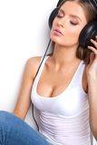 Sexy babe in white shirt and headphones listening music. Stock Image
