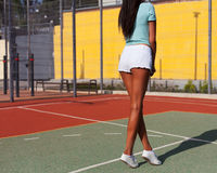 A sporty suntanned long-legged brunette posing with her back on a basketball court in shorts and a T-shirt. Freedom, love, vacatio Royalty Free Stock Photography