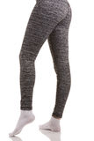 Back view of fit woman legs in white socks standing in one leg and another bended in knee in grey patterned thermal pants. On white isolated background royalty free stock photos