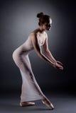 Sexy ballerina dancing in studio, on gray backdrop Royalty Free Stock Photos