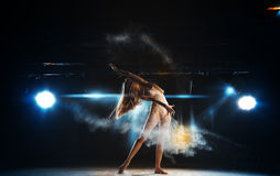 Sexy ballerina on stage posing against the backdrop of the spotl Stock Photos