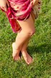 Sexy barefoot female legs. High angle view pair sexy shapely barefoot female legs posing on green grass as she holds aside fabric  long skirt Stock Images