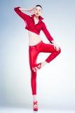 Sexy Baumuster mit dünner Karosserie kleidete im rotem Springen in das Studio an Stockfoto