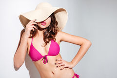 Sexy beach girl in hat wearing bikini over white background Stock Photos