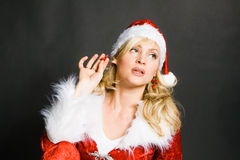 Beautiful blond girl. Dressed as Santa against black background royalty free stock photography