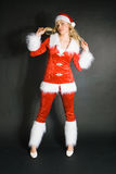 Sexy beautiful blond girl dressed as Santa. Against black background Royalty Free Stock Images