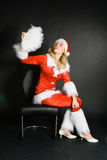 Sexy beautiful blond girl dressed as Santa. Against black background Stock Images