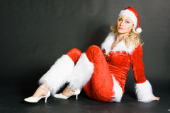 Sexy beautiful blond girl dressed as Santa. Against black background Royalty Free Stock Photography