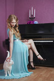 Sexy beautiful blonde girl in dress playing piano with a cat.  Stock Image