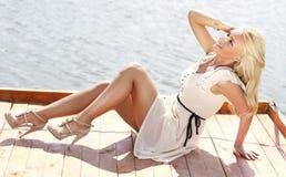 Sexy beautiful blonde on a lake pontoon Royalty Free Stock Photo
