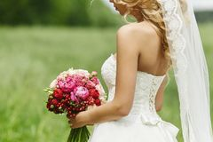 Sexy and beautiful blonde model girl with perfect body in wedding dress posing with a bouquet of flowers in her hands. Outdoors royalty free stock image