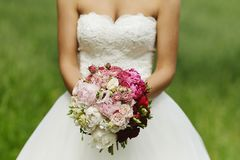 Sexy and beautiful blonde model girl with perfect body in wedding dress posing with a bouquet of flowers in her hands. Outdoors royalty free stock photos