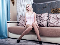 Sexy and beautiful blonde woman in erotic lingerie or corset and stockings posing on a sofa Royalty Free Stock Photos