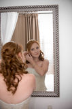 Sexy beautiful bride inserting her earrings. Red head sexy beautiful bride inserting her earrings in whilst smiling Royalty Free Stock Photography