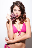 Sexy beautiful brunette holding grapes over white background Royalty Free Stock Image