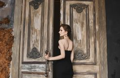 And beautiful brunette model girl with a trendy haircut and with bright makeup, in a fashionable black tight dress. Comes out through the vintage wooden doors royalty free stock image
