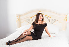 Sexy beautiful brunette woman lying in a bed Stock Image