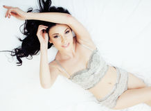 Sexy beautiful brunette woman lying in bed sensual gray lingerie, looking at camera. Seduction concept in luxury room Stock Photo