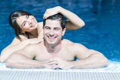 Couple in love by the side of the pool. Sexy beautiful couple in love relaxing in the water of a swimming pool Royalty Free Stock Photo