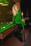 Sexy beautiful fashion model posing with the cue on pool table Royalty Free Stock Image