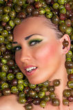 Sexy beautiful female face in the gooseberry Stock Image