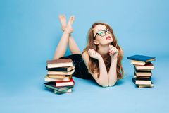 Female teacher reading book surprised gesturing. And beautiful female teacher in dress and eyeglasses, sitting on floor, posing and reading book, gesturing by royalty free stock image