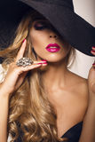 Sexy beautiful girl with blond hair in elegant black hat Stock Photos