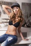 Sexy beautiful girl with blond hair in jeans and cap Royalty Free Stock Images