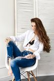 Sexy beautiful girl in jeans white shirt sitting on a chair. Gorgeous long hair and charming eyes young woman. Sexy Business lady. Is young and confident. Girl Stock Photo