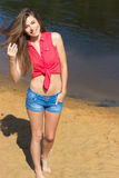 beautiful girl with long dark hair happy with the smile stands in denim shorts on the beach near the water on a Sunny day Stock Photos