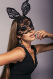 Sexy beautiful girl with long straight hair in black lace bunny mask. Fashion studio portrait of sexy woman with long straight hair in elegant black dress in Stock Images