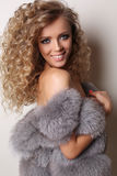 Sexy beautiful girl with luxurious curly hair wears fur coat Stock Image
