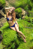 Sexy beautiful girl in swimsuit sitting on stones among the rocks in the jungle Royalty Free Stock Photos