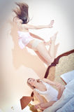 2 beautiful happy women in pajamas one of them jumping, while the other looking at her on the bed Royalty Free Stock Image