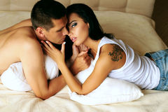 Sexy beautiful impassioned couple relaxing in bed at the hotel Stock Image