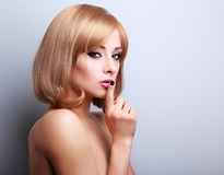 Sexy beautiful makeup blonde famale model showing secret sign on Stock Photography
