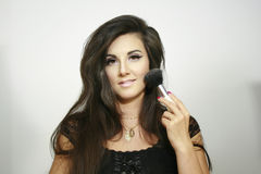 Sexy beautiful makeup girl  use big fluffy brush, looks at you with light smile Stock Images