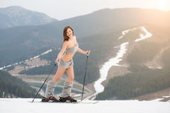 Sexy beautiful naked woman skier posing on the snowy slope of the mountain with ski equipment. Looking to the camera. Ski resort, ski lift, slopes and forest Stock Images
