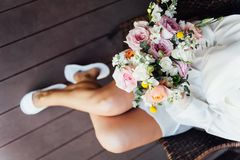 Beautiful nude brunette bride with bouquet and wavy hair style in white erotic underwear. Beautiful nude brunette bride with bouquet and bright smoky eyes make stock image