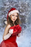 Sexy and beautiful Santa girl. In red Santa's dress and hat over winter forest background. Christmas card Royalty Free Stock Photo