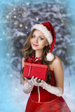 Sexy and beautiful Santa girl. In red Santa's dress and hat over winter forest background. Christmas card Stock Photos