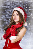 Sexy and beautiful Santa girl. In red Santa's dress and hat over winter forest background. Christmas card Royalty Free Stock Images