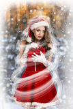 Sexy and beautiful Santa girl. In red Santa's dress and hat over winter forest background. Christmas card Royalty Free Stock Photography