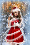 Sexy and beautiful Santa girl. In red Santa's dress and hat over winter forest background. Christmas card Royalty Free Stock Photos