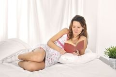 beautiful student woman lying on bed reading novel or studying book in relax Stock Image