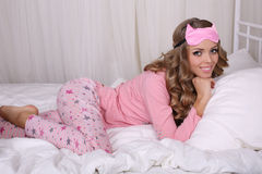 Sexy beautiful woman with blond curly hair in pajama lying in bed Stock Photos