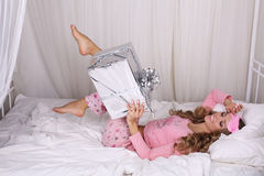 Sexy beautiful woman with blond curly hair in pajama with present Royalty Free Stock Photo