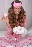 Sexy beautiful woman with blond curly hair in pajama with sweets Stock Photos
