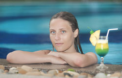 Beautiful woman relaxing in the pool with a cocktail Stock Photos